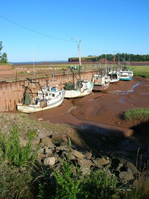 same pier and fishing boats at a Bay of Fundy low tide- Nova Scotia, in the Cape Blomidon area