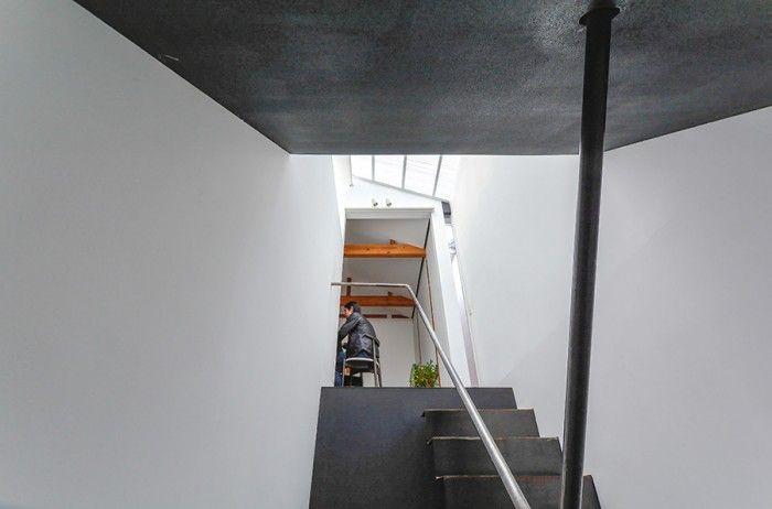 階段室から2階のリビングダイニングを見上げる。黒と白の仕上げのコントラストが際立つ空間。