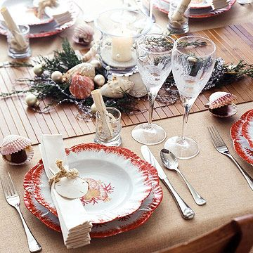 Seaside Serenity Table - At this beach house table, the bamboo-slat runner is reminiscent of a stroll along the boardwalk. Shell-pattern dishes and etched stemware evoke an underwater theme. Fan-folded napkins are tied with rope and adorned with sand dollars.
