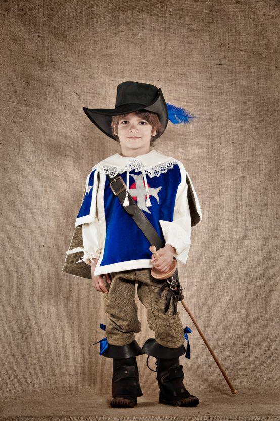 """Costume de mousquetaire du Roi inspiré du 17ème siècle composé de 3 pièces : Le pantalon en velours chenille réglable à la taille, la chemise en lin écru agrémentée de dentelles, la casaque en velours lisse et doublée du velours chenille assorti au pantalon.  Ce costume de fabrication artisanale est disponible du 4 au 12ans à partir de 223€. Tous les accessoires en cuir et en bois sont également disponibles sur le site de """"7 et une Lieues"""""""