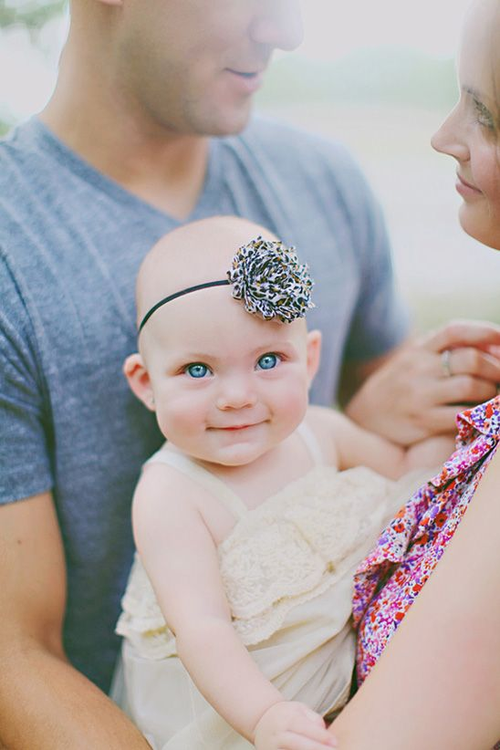 baby looking at cam, mom and dad looking at each other.  great capture of her blue eyes