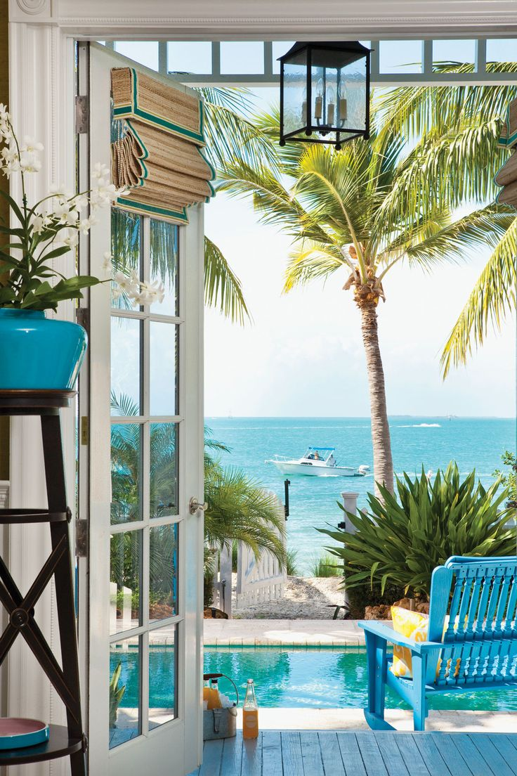 French doors open onto this home's rear exterior, where a view of the ocean can be seen beyond the pool. The only additions here were fresh landscaping and new outdoor furnishings including custom-painted rocking chairs. Bamboo shades from Elite Creation provide an alternative to draperies.