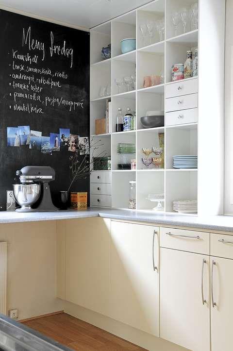 TAVLEFINT.På den ene kjøkkenveggen har eierne brukt en kombinasjon av hyller og små skuffer til oppbevaring av servise og annet kjøkkenutstyr. Den andre veggen er dekket av en tavle som brukes til handlelister, ukesmenyer og minnerike familiebilder.