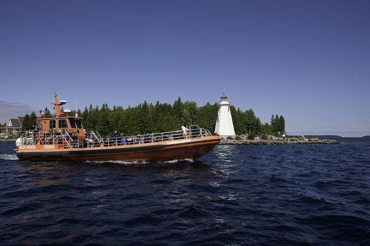 The Flowerpot Express passes Big Tub Lighthouse on its way to Flowerpot Island. Tobermory Ontario Canada.  www.blueheronco.com for details.