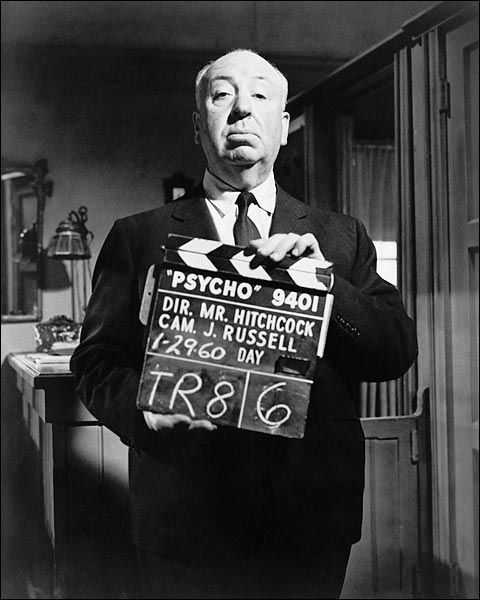 Alfred Hitchcock standing on movie set, holding clapper boards for his classic horror film 'Psycho'.     PHOTOGRAPHER / CREDIT: New York World-Telegram & Sun Collection  DATE: 1960