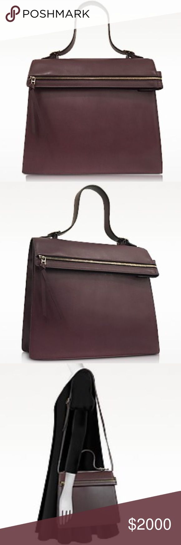 """VICTORIA BECKHAM Topaz Burgundy Leather Handbag Topaz Burgundy Leather Handbag crafted in natural smooth calfskin has clean lines and a contemporary design that looks great paired with a pencil skirt or pant suit. Featuring flap top closure, single top handle, detachable and adjustable shoulder strap, internal zip pocket, metal zip on front flap and gold tone hardware. Signature dust bag included. Made in Italy.Calfskin Width12.60"""" 