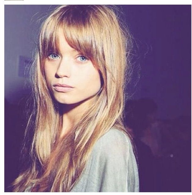 Long hair with long fringe, tapered from lash length to cheekbone length or maybe layers all the way down front of hair. Wide face shape, high forehead.