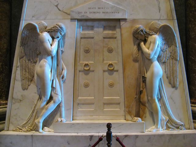 """""""Sepolcro degli Stuart"""", Antonio Canova, 1817-1819; scultura in marmo; realizzata in memoria di Giacomo III e dei figli Carlo Edoardo ed Enrico cardinale, si trova all'interno della Basilica di San Pietro, Città del Vaticano."""