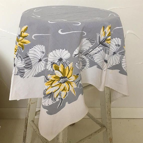 This small, square, vintage printed tablecloth features yellow florals and white fanned palm leaves on a gray and white background. Circa 1940s or 1950s. Midcentury tablecloth, with hemmed ends and woven selvage sides. The tablecloth measures 34 x 30. Excellent for kitchen, cafe,