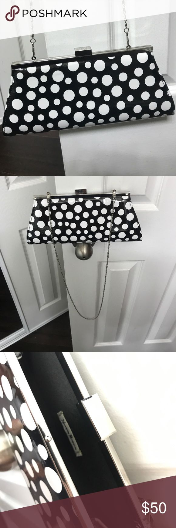 Neiman Marcus Polka Dot Clutch Black and white Polka Dot clutch with a silver accent top and silver strap chain. Never been used, excellent condition, nothing has been inside of it. Great for all occasions, can be used as a cross body or clutch. Neiman Marcus Bags Clutches & Wristlets