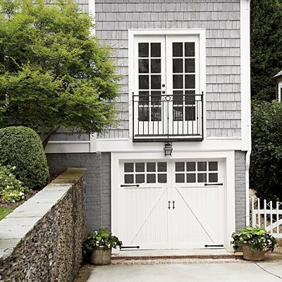 Grey brick and shingles, Juliet balcony, French doors, lantern sconce, and strap hinges on carriage-style garage; Ross Piper