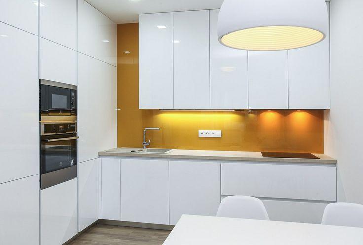 Výrazně žlutý je i skleněný obklad nad pracovní plochou kuchyňské linky.