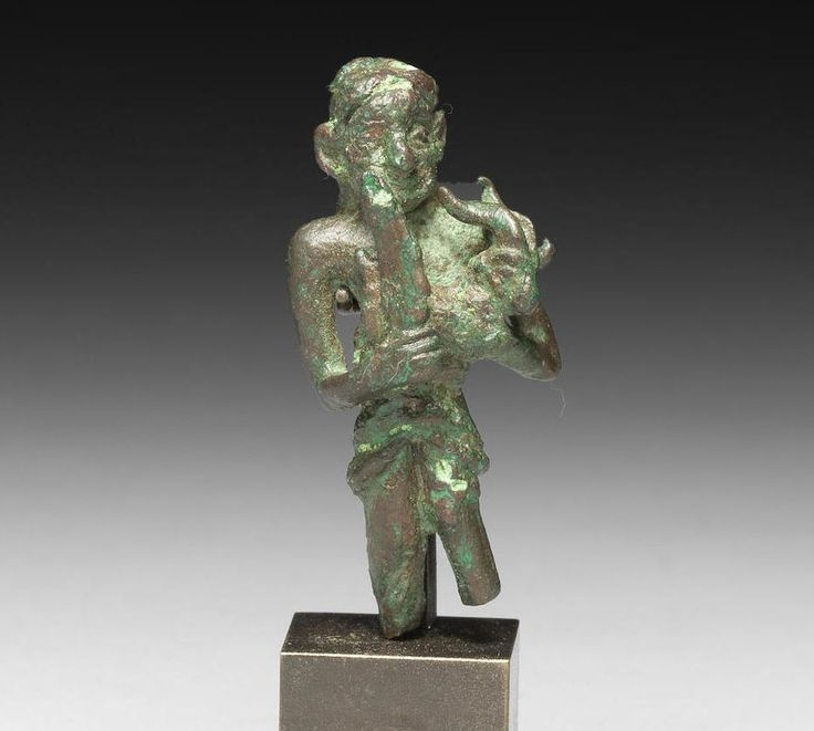 Elamite bronze figure of a sacrificing man  Iran, 3rd millennium B.C. The stylised draped figure with rimmed eyes and wide smile, the ears and nose oversized with the hair incised at the back, the bent arms cradle a goat for sacrifice, 5 cm high. Private collection