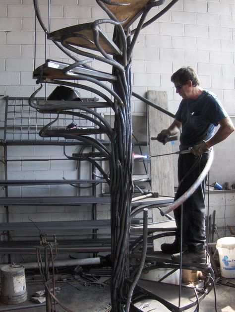 Hand forged iron work for a spiral staircase. Laying in vinework with torch.