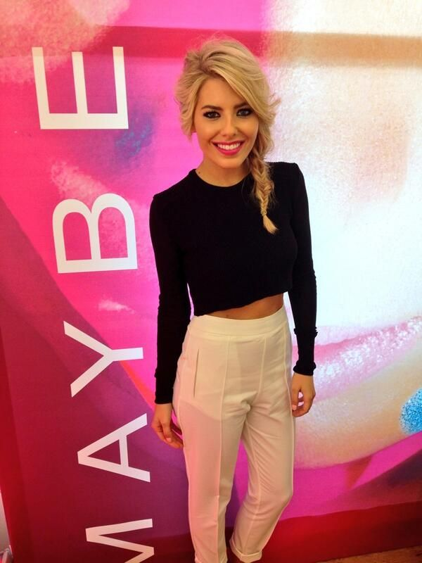 Mollie King wearing a vintage black long sleeved crop top and cream high waisted trousers