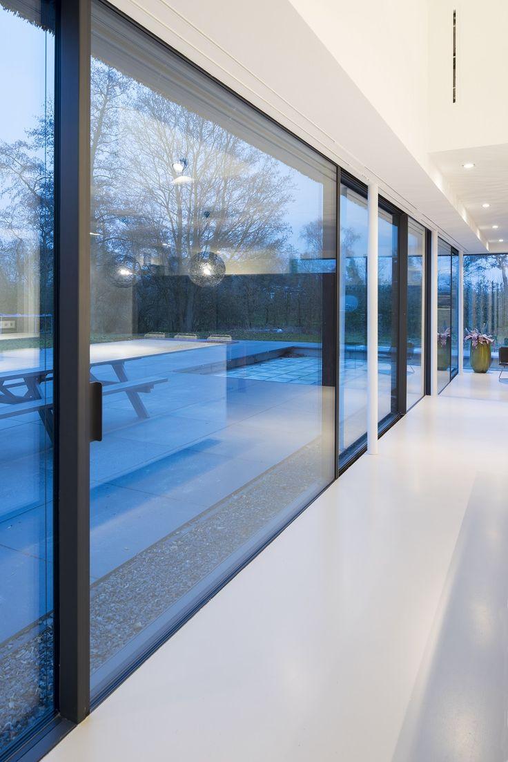 De glazen pui beslaat 16 meter, daarna gaat hij nog eens 4 meter rechts de hoek om; in totaal is 50 m2 drievoudig glas gebruikt. De profilering volgt het hoogteverschil tussen de woonkamer en keuken en is volledig weggewerkt in de vloer en in het plafond.