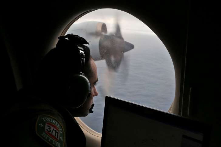 In this March 22, 2014 file photo, flight officer Rayan Gharazeddine on board a Royal Australian Air Force AP-3C Orion, searches for the missing Malaysia Airlines Flight MH370 in southern Indian Ocean, Australia. (AP Photo/Rob Griffith, File)