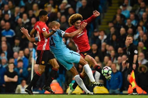 Manchester United's Belgian midfielder Marouane Fellaini battles with Manchester City's Belgian defender Vincent Kompany during the English Premier...