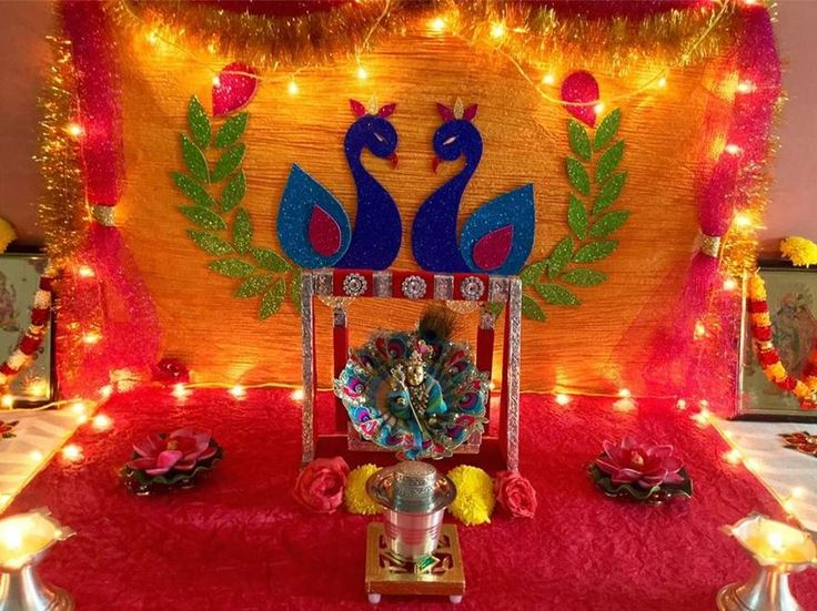 Go for this cute colourful Janmashtami decoration. Use crêpe paper for the background. Paste peacock cutouts and hang LED lights and streamers around it.