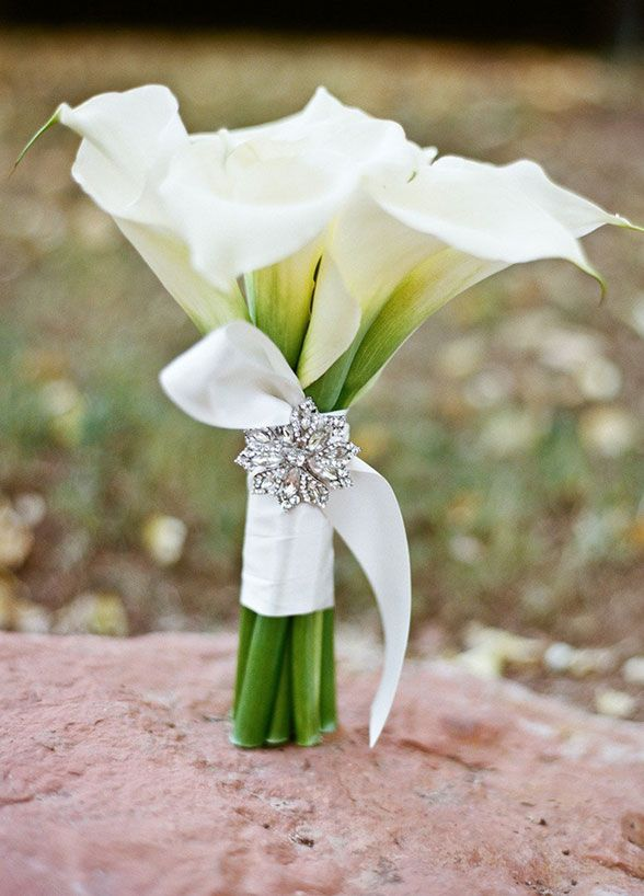 The brooch adds sparkle to this simple elegant white calla lily bouquet.
