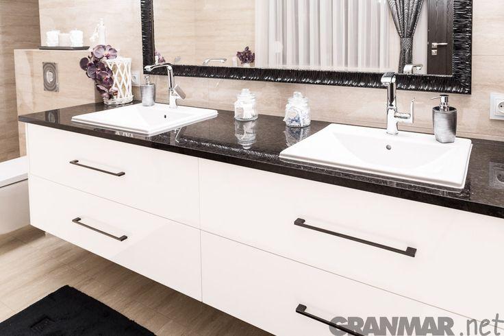 Łazienka z blatem z granitu Antic Brown. Ciepły odcień kamienia delikatnie koresponduje z bielą szafek i umywalek