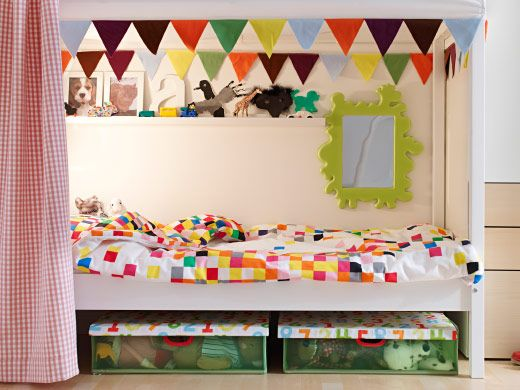 IKEA - Child's bed with colorful printed duvet cover and pillow, a shelf, a mirror and underbed storage