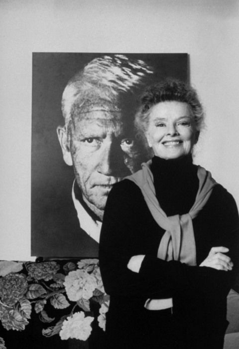 Katharine Hepburn standing in front of a poster size photo (her favorite, taken by Phil Stern) of actor Spencer Tracy...