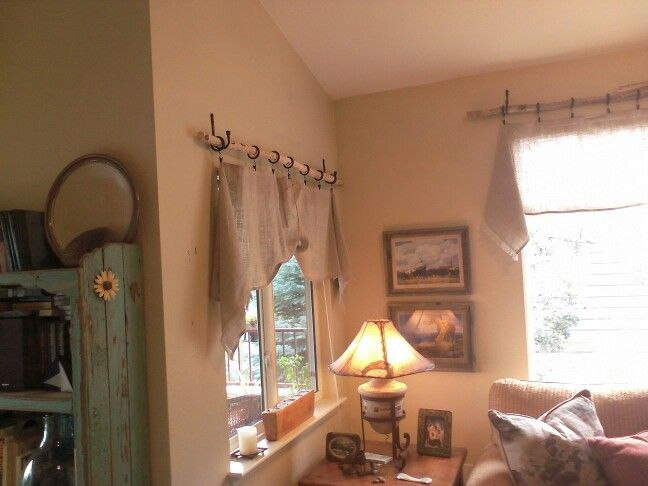 Rustic valance made of burlap table runners, branches, clip on curtain rings and curtain tie backs for the brackets.