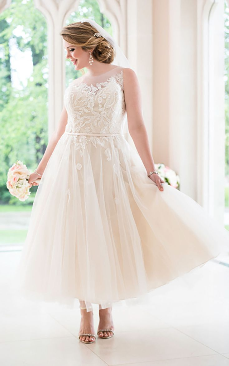 Tea-length tulle wedding gown from Stella York features lace appliques on its illusion neckline and back, fitted bodice and full skirt.