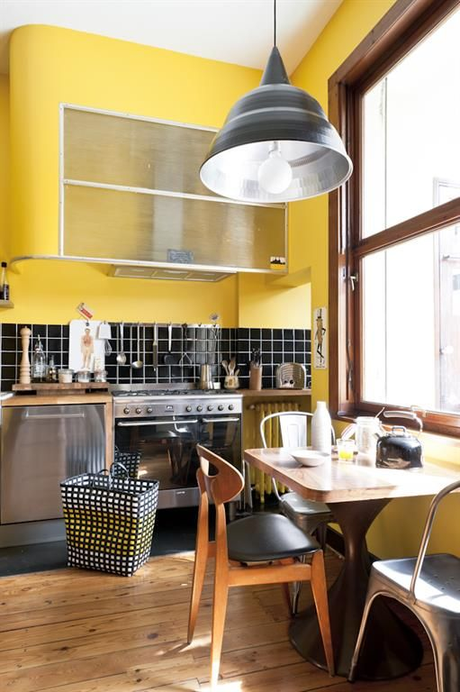 Very modern kitchen with bright yellow on the wall and black tiles | Cuisine très moderne aux murs jaunes et crédences noires.