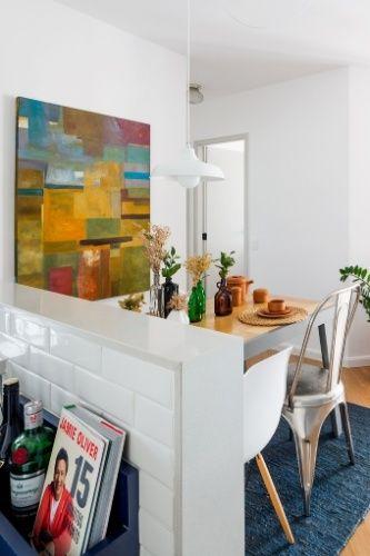 Inspiração de decor para apê pequeno: balcão dividindo sala e cozinha. Nele são apoiadas garrafas de bebidas e livros, do lado da cozinha.