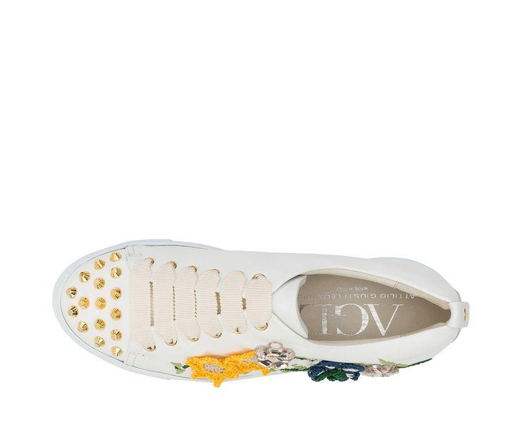 Fiori colorati dall'effetto pop-up, realizzati a mano con la tradizionale lavorazione del crochet, impreziosiscono la sneaker sporty chic. I raffinati ricami di cotone colorato e i lucenti cristalli si combinano con maxi borchie oro, combinando praticità