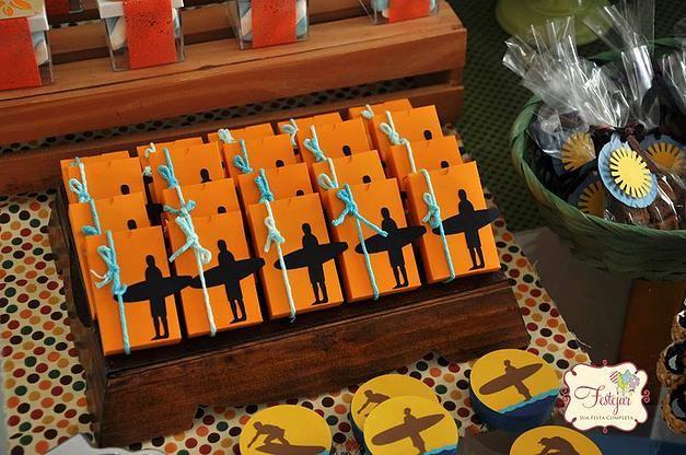 A silhueta de surfista decora as latinhas de balas e os chocolates da mesa do bolo nessa festa com o tema Surf para menino