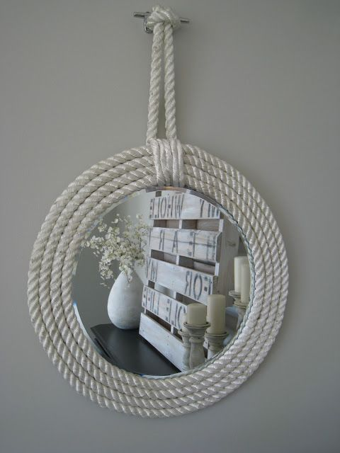 http://www.thelilypadcottage.com/2012/09/nautical-rope-mirrors.html  mirror charger ($), glued to large sturdy foam board.  cut slit on top of foam board for later.  glue rope onto foam board, cover unsightly end of rope circles w/ thinner (unravel bigger rope to get thinner rope), hang on decorative hook (or dock cleat  used here)