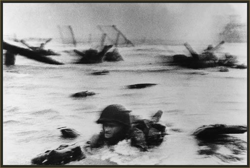 """""""Robert Capa — Landing of the American troops on Omaha Beach""""  When photographers start laying it on thick about the absolute importance of shooting """"tack sharp"""" images, this image usually comes to mind."""