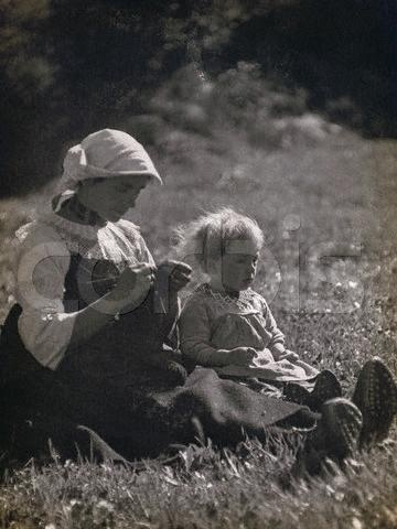 ca. 1931 --- Mother and daughter sitting in a meadow. The woman is knitting. --- Image by ? Alinari Archives/CORBIS