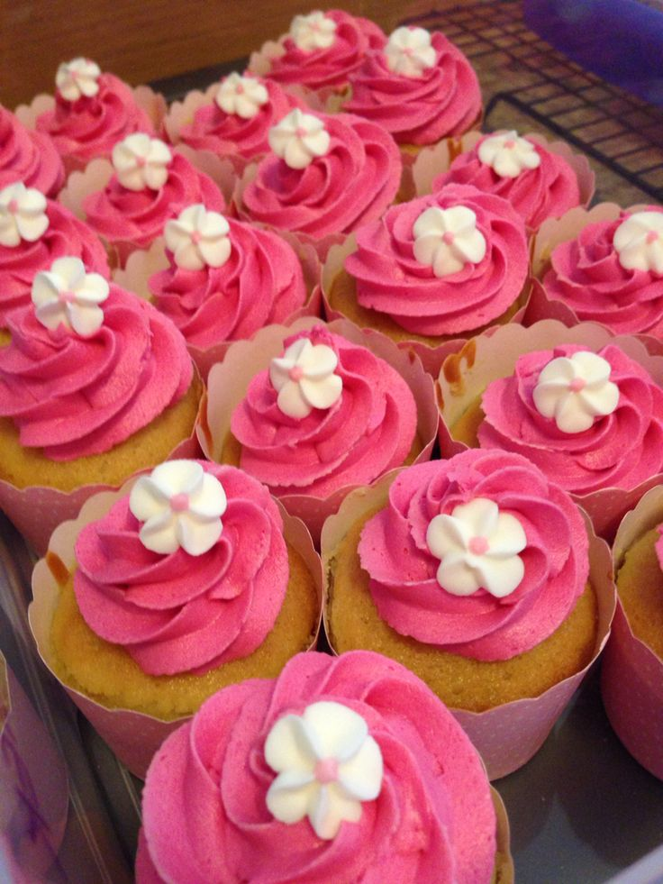 Vanilla cupcakes decorated with Pink buttercream topped with sugar frangipanis