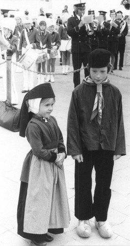Twee kinderen in Terschellinger klederdracht aan de haven ter ere van de aankomst van het koninklijk bezoek aan Terschelling, 7 mei 1974 (fotonummer 32943).