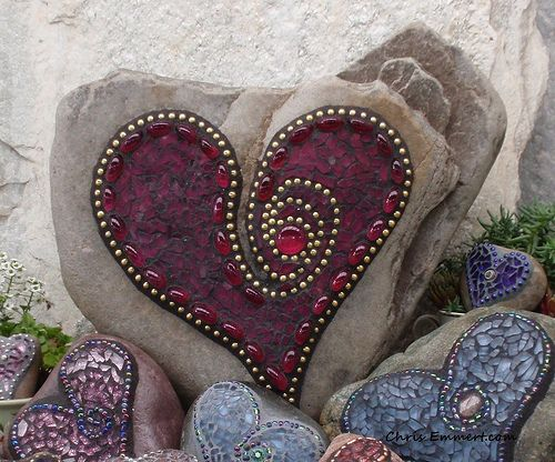 Lavender, maroon, and blue mosaic garden stones, photo by Chris Emmert via Flickr.  Not sure how to adhere the designs well enough to survive, but certainly doable.