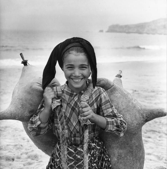 A young girl carrying waterbags on the beach at Nazare Portugal