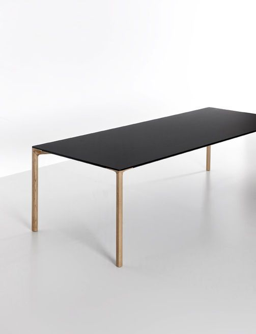The second iteration of the Boiacca table that LucidiPevere designed for Kristalia recasts its slim concrete silhouette with wood legs and white laminate or black Fenix-NTM top.
