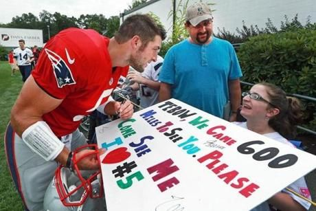 """""""Tim Tebow's Bond with Fans is Unique"""" The Boston Globe August 5, 2013 After asking her name, Tim Tebow autographs the poster of wheelchair-bound Madelin Beardsley of Virginia Beach."""