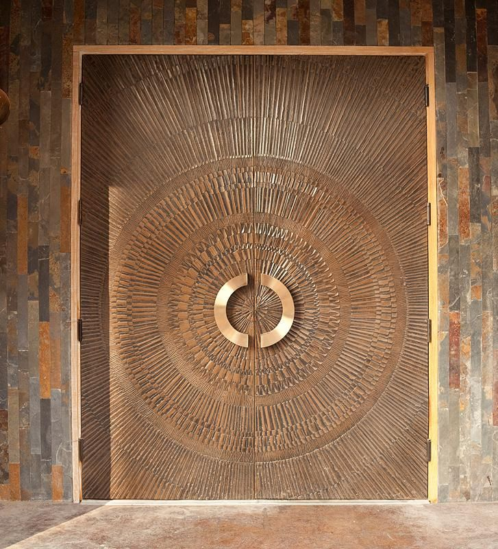 Bonded Metal Doors in Bonded Bronze with Natural patina and Corona pattern and Ara door pulls in Polished Bronze
