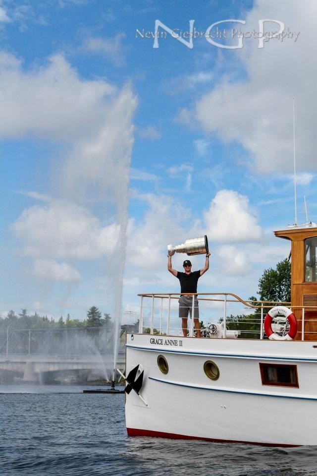 Mike Richards holding the Stanley Cup aboard the Grance Anne II in front of the Rotary Goodwill Geyser in Kenora.