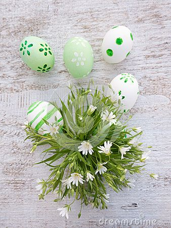 White and green easter eggs decorated by stripes, dots and flowers and wild flowers bouquet on the white wooden board