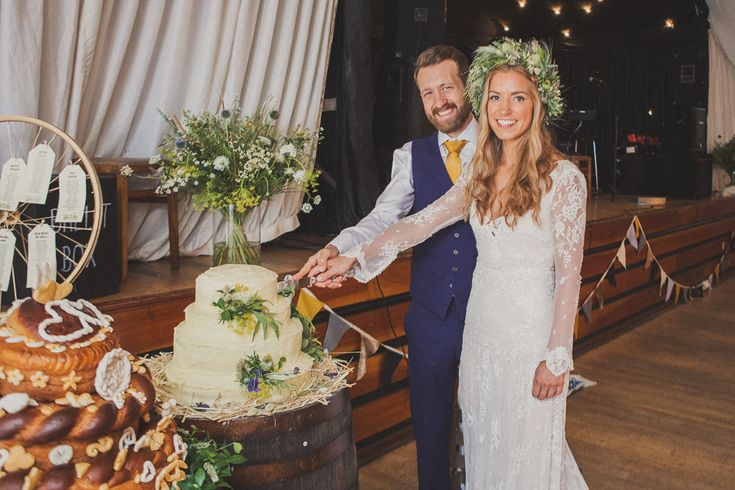 Bride in Inbral Dror Wedding Dress & Groom in Navy Beggars Run Suit - Mr & Mrs Photography   Pre-Owned Inbral Dror Wedding Dress   Jimmy Choo Shoes   Wild Flowers & Bunting Decor Traditional Ukrainian Wedding   White Bridesmaid Dresses