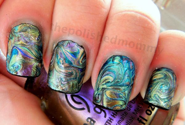 Wow. Apparently you do this by dragging a needle through nail polish. It looks like the inside of an abelone shell.