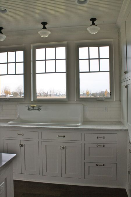 Six pane windows over a farm style sink, marble counters and sills, subway tile backsplash, beadboard ceiling and pendant lighting.