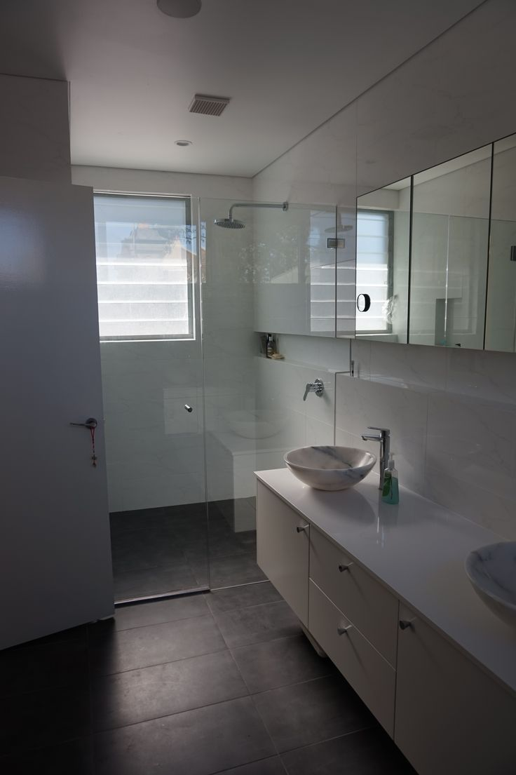 Ensuite bathroom with large frameless shower, no door wall hung vanity, shaving cabinetry with mirror doors Basin brought back from Bali Recessed spaces above vanity and in shower