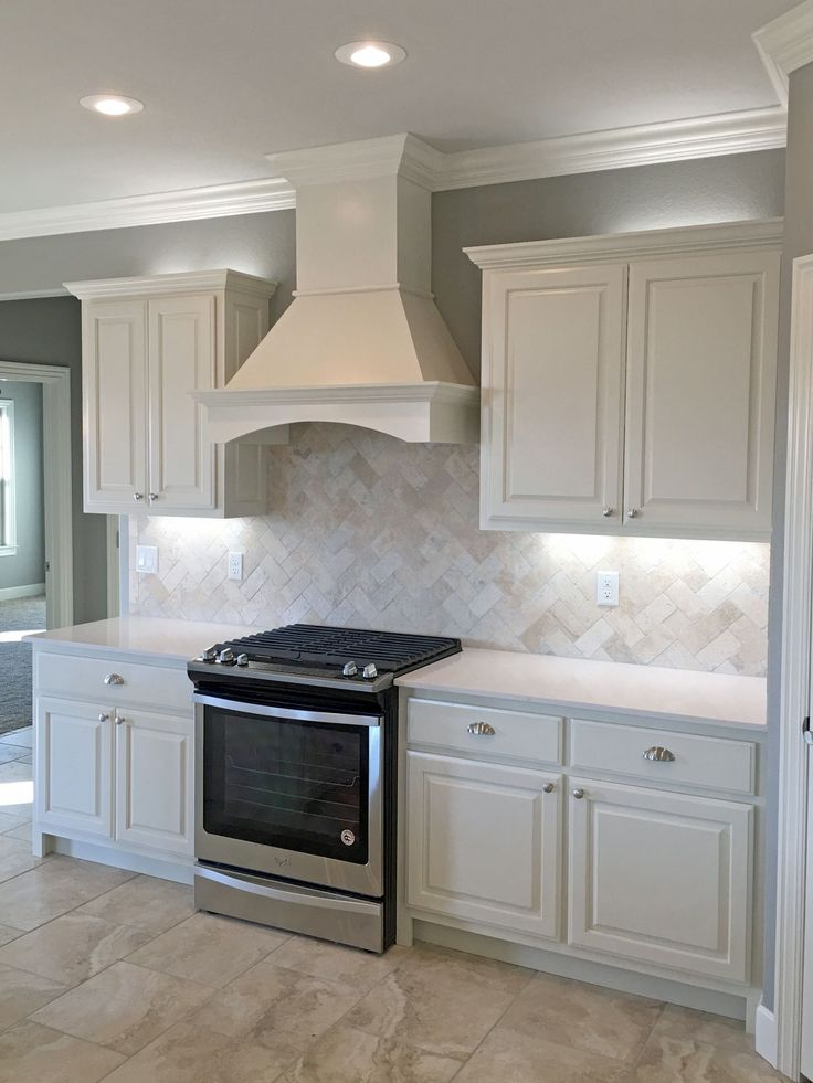 White kitchen with satin nickel fixtures, pendant lights, travertine backsplash, white quartz countertops, wood range hood